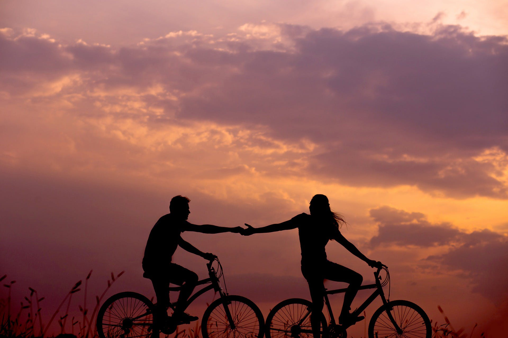 Couple cycling and holding hands