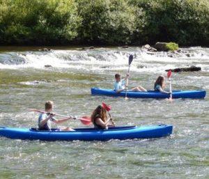 People kayaking down a river
