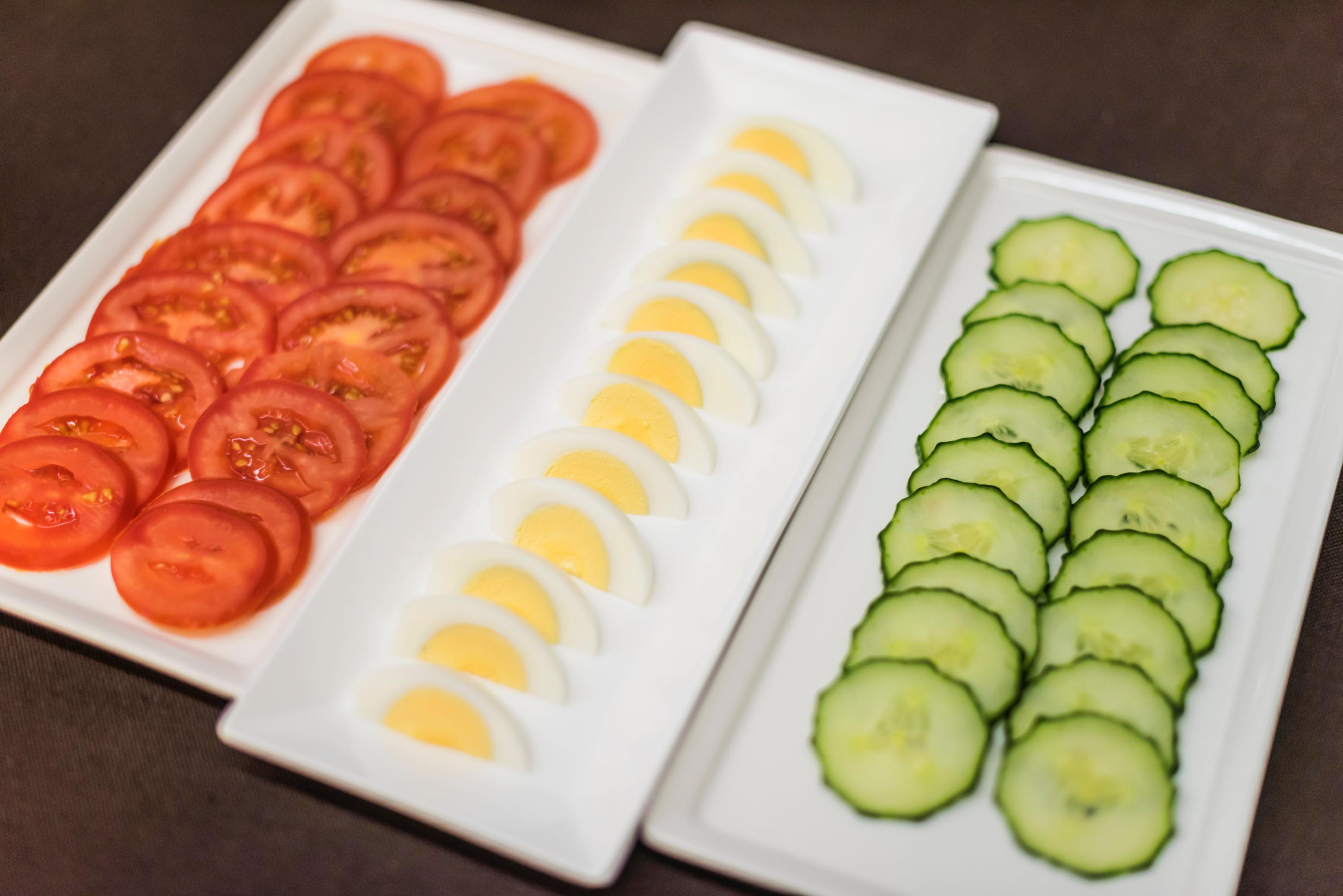 Trays with sliced tomatoes, eggs, and cucumber