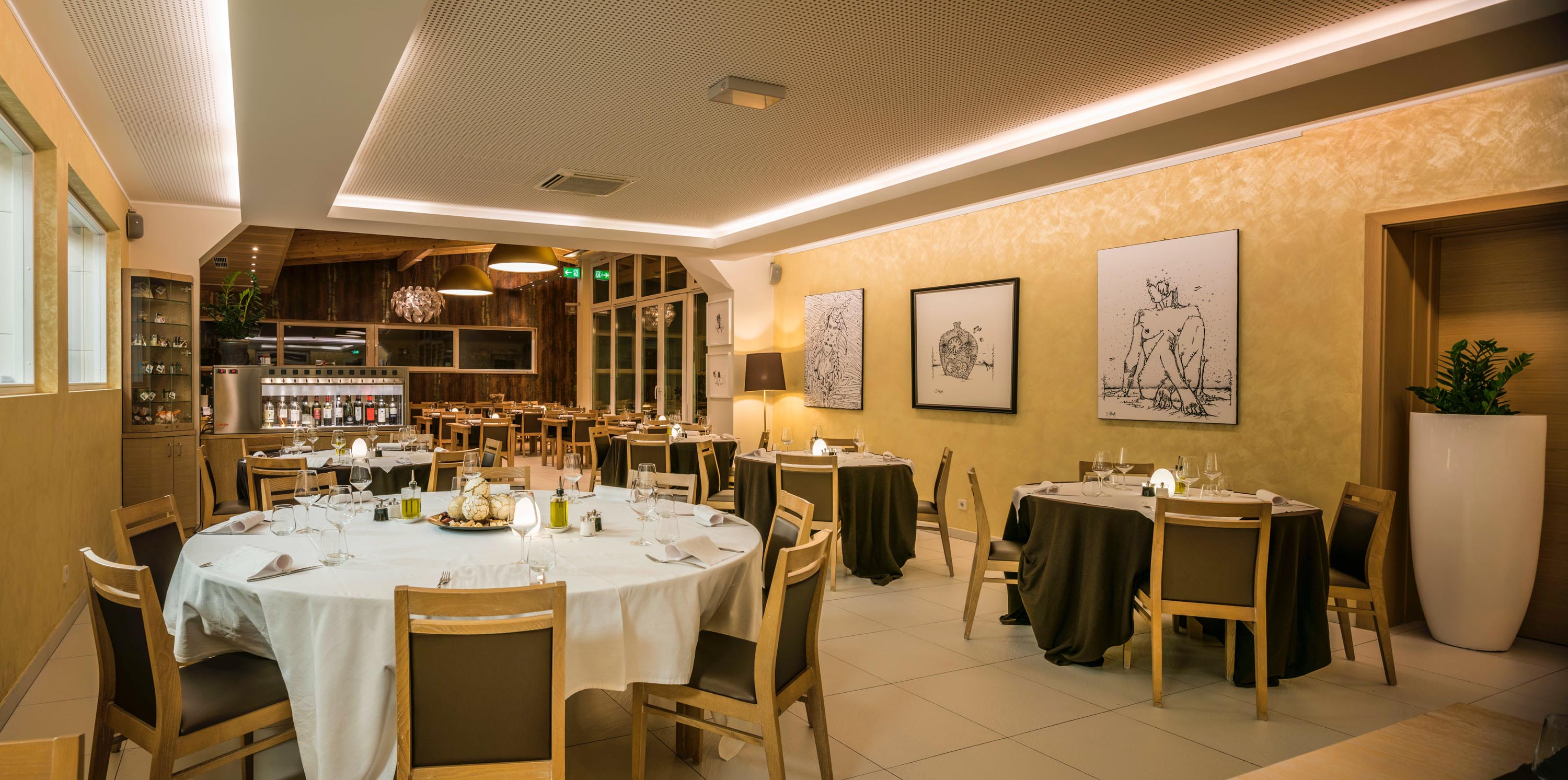 Tables in a restaurant with paintings on the walls