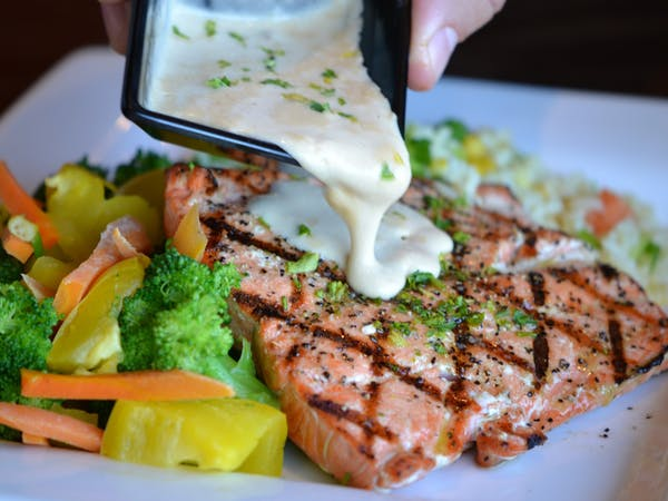 Person pouring sauce onto grilled salmon with vegetables